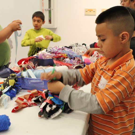 A young student named Gustavo, in orange shirt, works on his sock bundles for the group sculpture.