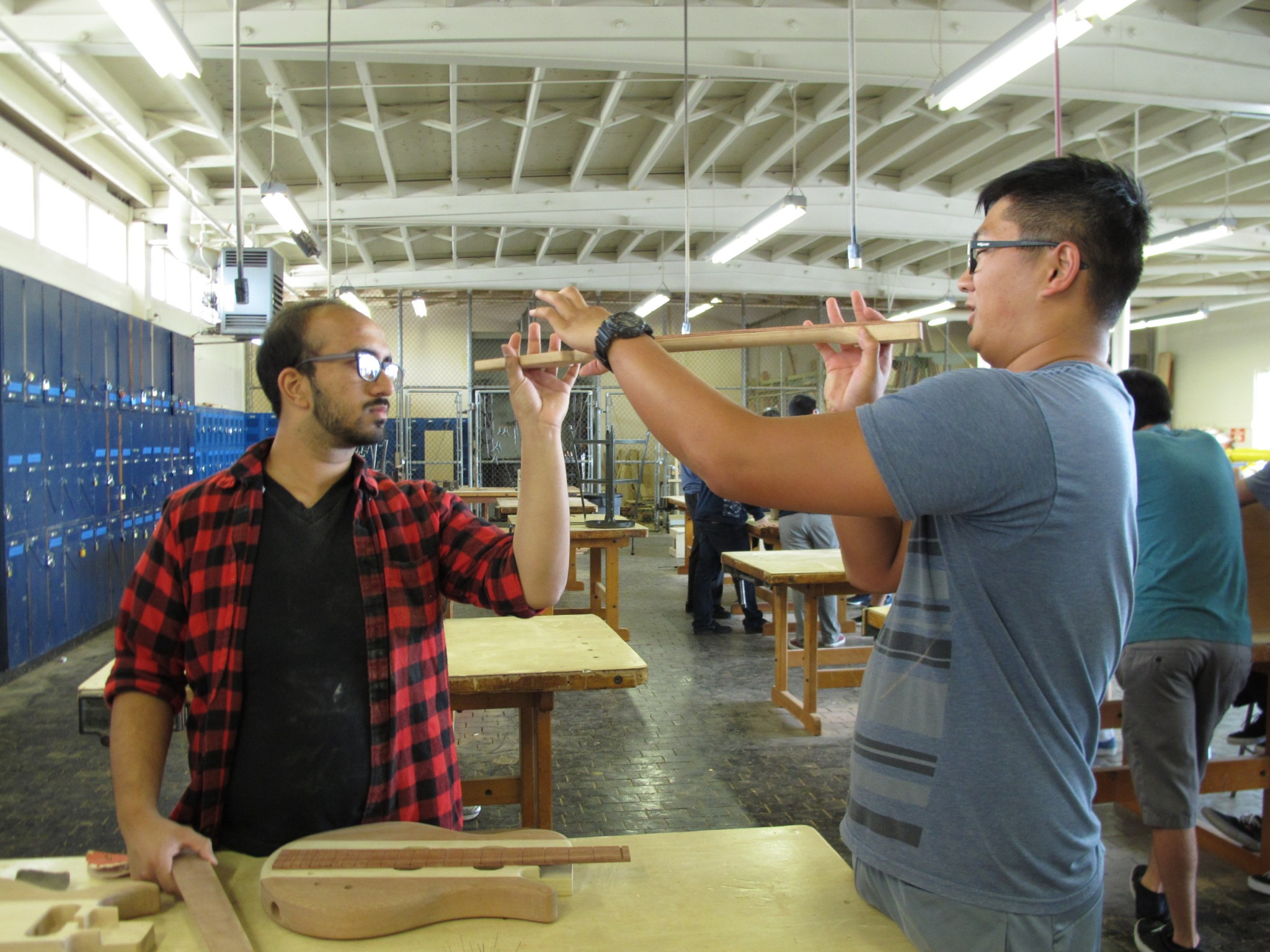 Senior Timothy Lee (right) checks out the curve on his fret board with a little help from classmate Farhan Saleh. The two are taking wood shop and physics at Camarillo High School as part of the STEM Guitar Project.
