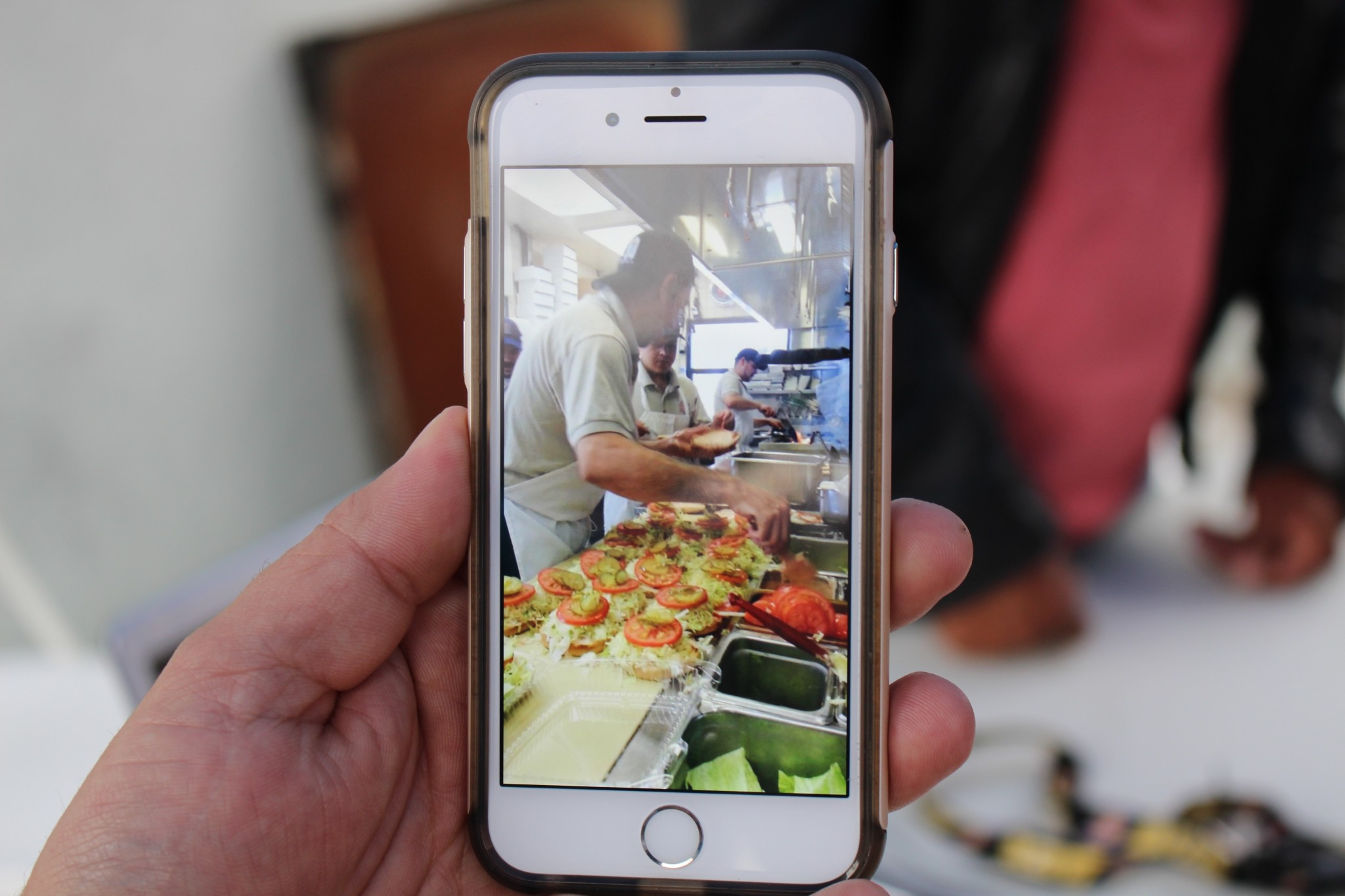 Primo Jimenez holds up his phone, showing a photo of him flipping burgers at work. Vericose veins have made it too painful to stand. (Photo: Karen Foshay)