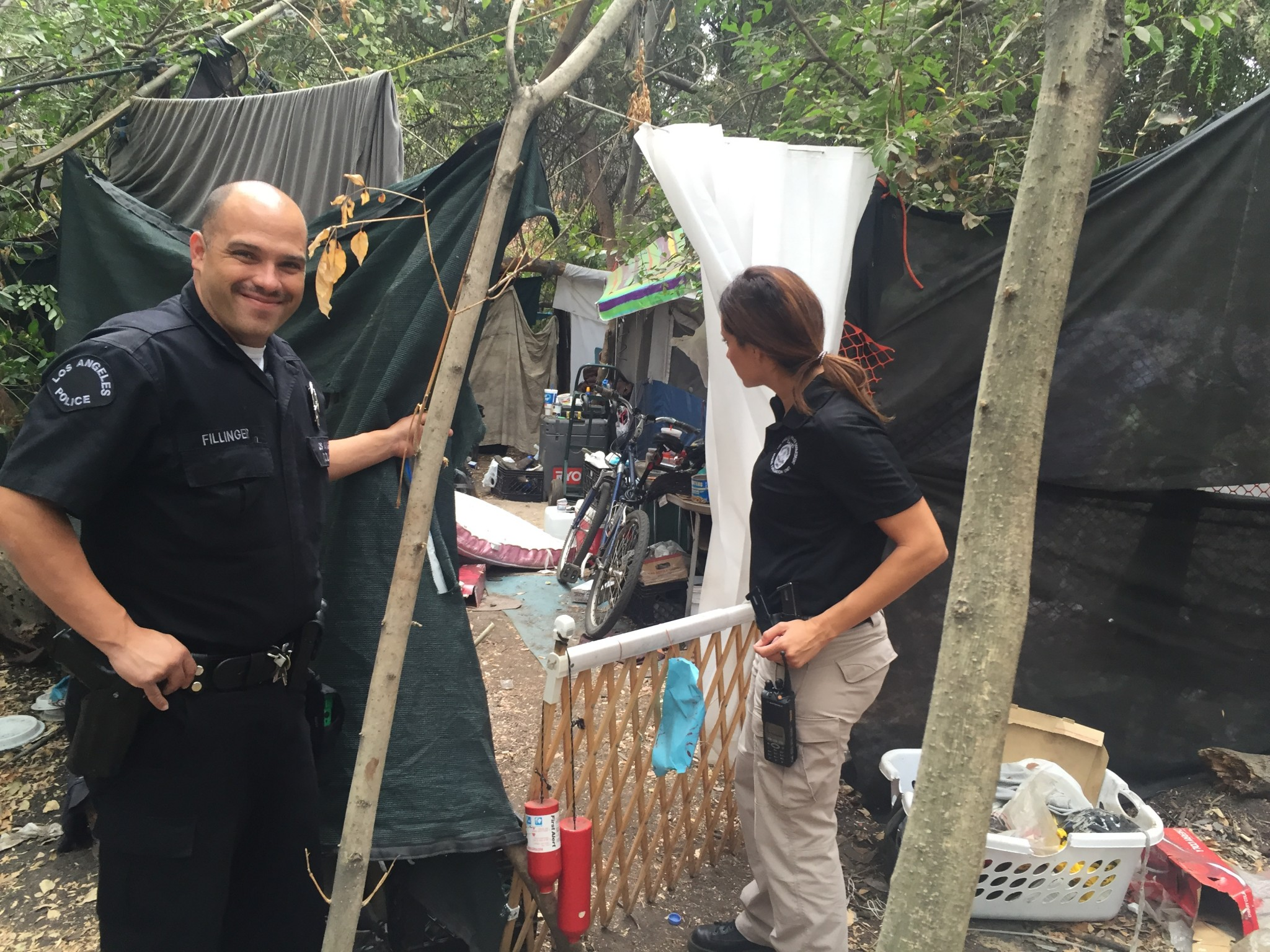 LAPD Officer Josh Fillinger and an LAPD mental health specialist look inside a homeless encampment. (Photo: Anna Scott)