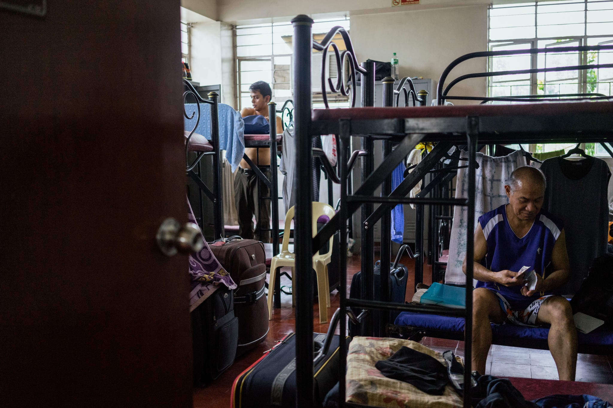 Filipino seafarers are seen in their room in the Apostleship of the Sea dormitory, a place where seafarers can stay for a low price while waiting to be employed in a ship. The Apostleship of the Sea is a Catholic organization that supports and provides services for vulnerable seafarers worldwide. (Photo: Hannah Reyes Morales)