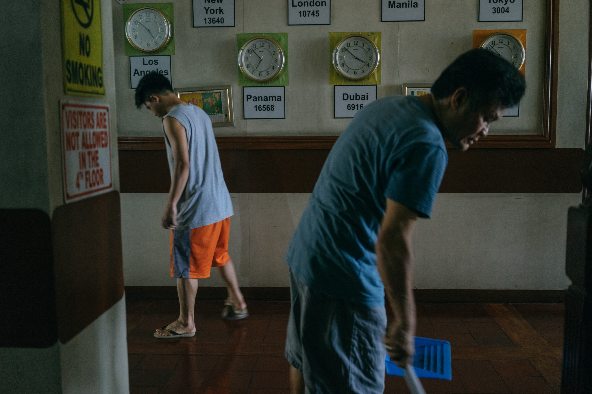 Men clean the floors inside the Apostleship of the Sea dormitory, a place where seafarers can stay for a low price while waiting to be employed in a ship. The Apostleship of the Sea is a Catholic organization that supports and provides services for seafarers who are often vulnerable to abuse. (Photo: Hannah Reyes Morales)