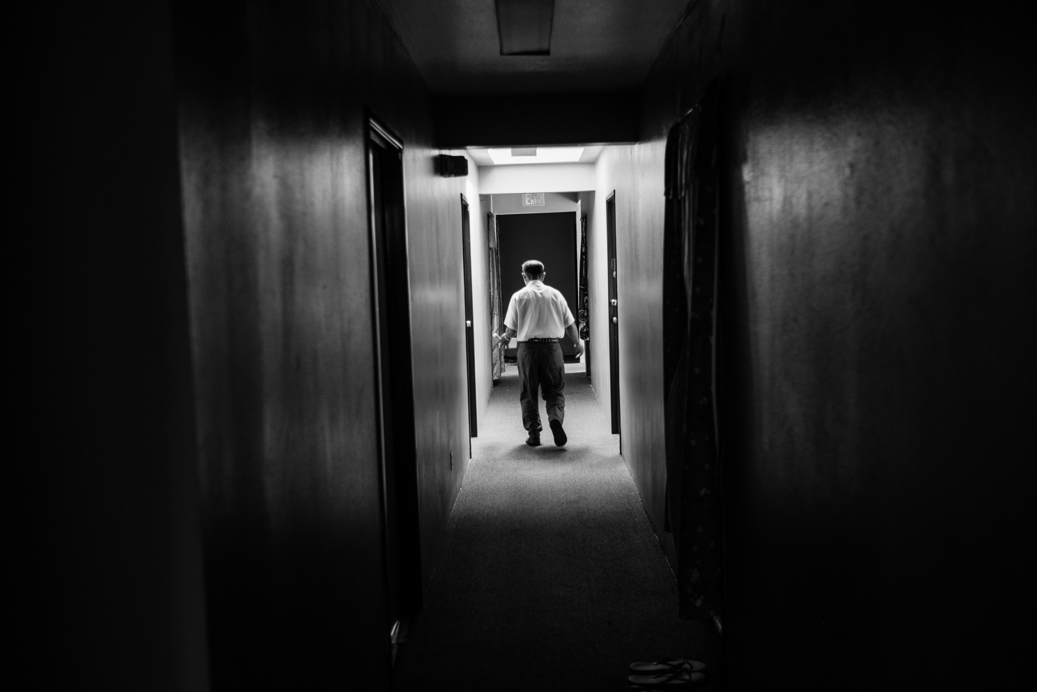 A senior resident of a Chinatown SRO apartment building walks down a hallway, lit only by a single skylight. (Photo by Bear Guerra)