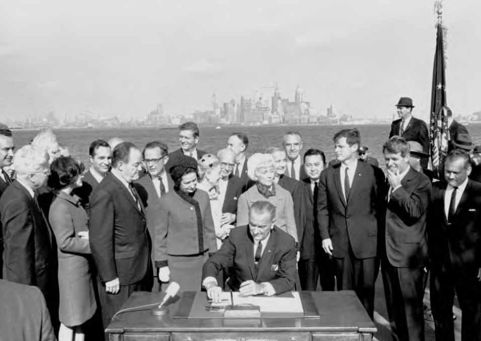 Image result for lbj signs new immigration act under the statue of liberty